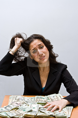 Financial stress stock photo, Business woman pulling hair and stressed about finances. Sitting at a table with lots of money. Isolated on a white background by Paul Hakimata