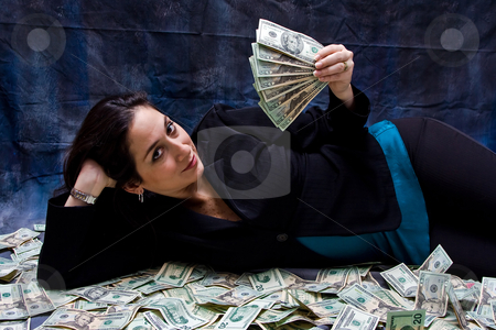 Rich woman stock photo, Rich business woman waving money and laying with her money isolated on a dark background by Paul Hakimata
