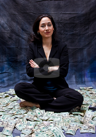 Woman sitting in money stock photo, Rich woman sitting with crossed arms in money isolated on a dark background by Paul Hakimata