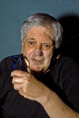 Senior man with glasses stock photo, Dramatic portrait of a senior man with a pair of blue glasses in his hand wearing a black shirt isolated on gray/blue by Paul Hakimata