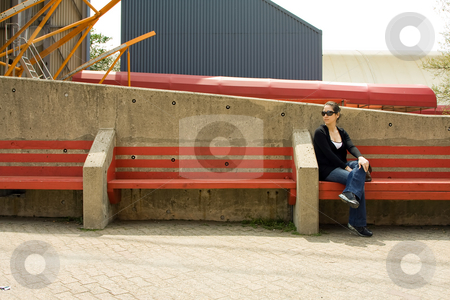 Woman on red bench stock photo, Beautiful young woman sitting/waiting on a red bench on a bright day, wearing sunglasses. by Paul Hakimata