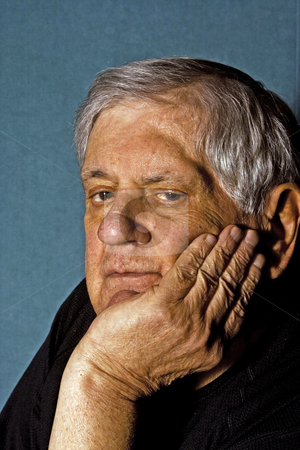 Senior man stock photo, Dramatic side portrait of a senior man with his hand on the side of his face wearing a black shirt isolated on gray/blue by Paul Hakimata