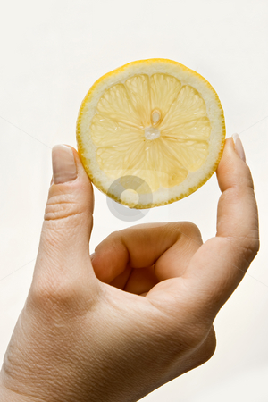 Lemon slice in hand stock photo, Woman hand holding up a wedge of lemon, isolated on white by Paul Hakimata