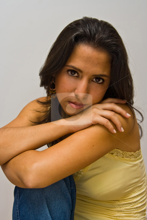 Beautiful latina stock photo, A beautiful dark brown haired latina woman wearing a yellow shirt and arms crossed on top of her knee, isolated on white by Paul Hakimata