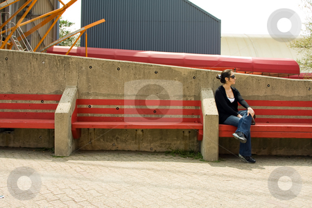 Woman on red bench stock photo, Beautiful young woman sitting/waiting on a red bench on a bright day, wearing sunglasses by Paul Hakimata