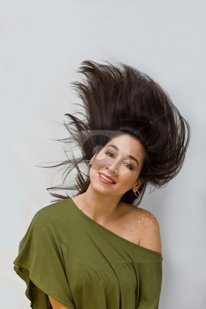 Swinging hair stock photo, Beautiful woman in a green shirt swinging her dark brown hair around, isolated on white by Paul Hakimata