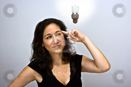 The environment idea stock photo, Woman who just came up with a great environmentally friendly idea. Pointing up her finger at her head and having a fluorescent idea bulb hanging above her head by Paul Hakimata