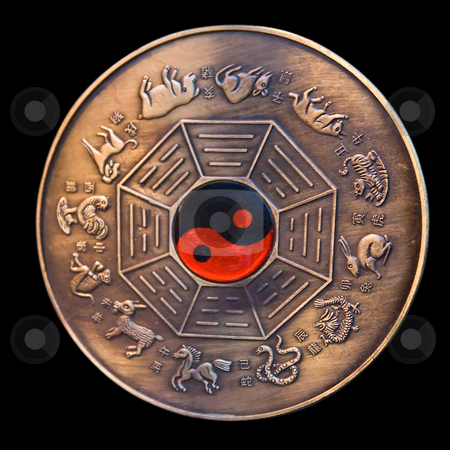 Lunar calendar stock photo, Lunar calendar depicted in a bronze medallion with a red and black ying yang in the middle, isolated on black by Paul Hakimata