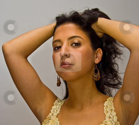 Latina with hands in hair stock photo, Beautiful dark brown haired latina woman with both her hands in her hair, wearing a yellow shirt, deep red glossy lips and gold eyeshadow, isolated on white by Paul Hakimata