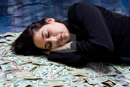 Woman dreaming about money stock photo, Rich business woman laying with her money as she dreams about it isolated on a dark background by Paul Hakimata
