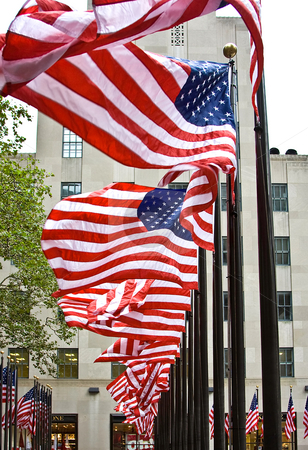 Row of American flags stock photo, Wind is blowing through a row of American flags at the Rockefeller Center in New York City by Paul Hakimata