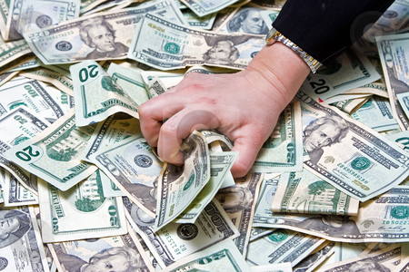 Greed stock photo, Womans hand grabbing money from a huge pile of dollars by Paul Hakimata