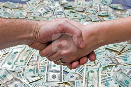Done deal stock photo, Two shaking hands above a layer of lots of money by Paul Hakimata