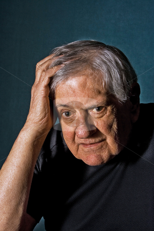Stressed/Confused senior man stock photo, Dramatic portrait of a senior man with his hand on the side of his face and in his hair wearing a black shirt isolated on gray/blue by Paul Hakimata