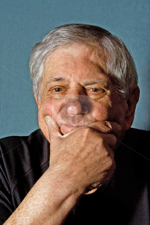 Senior man stock photo, Dramatic portrait of a senior man with his hand on his chin wearing a black shirt isolated on gray/blue by Paul Hakimata