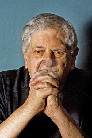 Senior man stock photo, Dramatic portrait of a senior man with his hands in front of his chin in praying grip wearing a black shirt isolated on gray/blue by Paul Hakimata