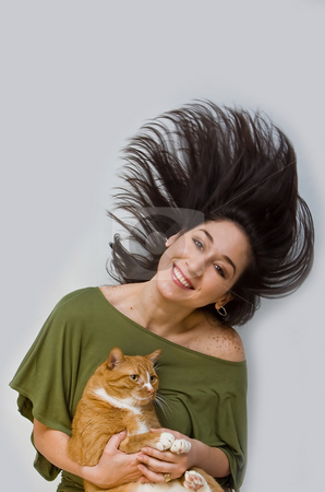 Woman holding cat stock photo, A woman with big smile in green shirt swinging her dark brown hair around while holding an orange cat, isolated on white by Paul Hakimata