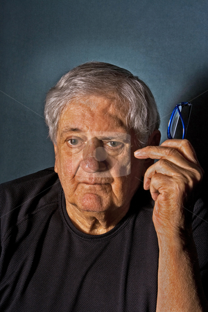Senior man with glasses stock photo, Dramatic side portrait of a senior man with a pair of glasses in his hand next to his face wearing a black shirt isolated on gray/blue by Paul Hakimata