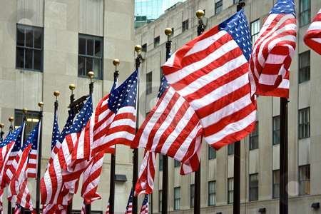 A row of American flags stock photo, Wind is blowing through a row of American flags at the Rockefeller Center in New York City by Paul Hakimata