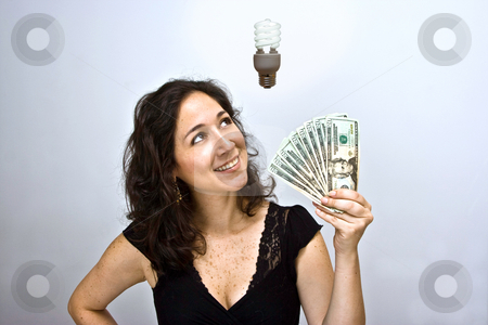 Energy saving money stock photo, Woman waving money and looking up. Having an environmentally friendly idea with an energy saving fluorescent light bulb floating above her head, on a white background by Paul Hakimata