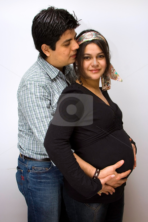 Parents expecting.... stock photo, Parents expecting a baby. Father holds the belly of the mother and mother placed her hands on top of fathers hands. by Paul Hakimata