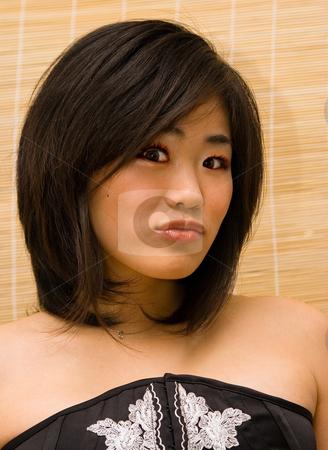 Beautiful Oriental woman stock photo, Beautiful Oriental woman's headshot on a bamboo curtain background by Paul Hakimata