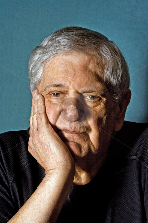 Senior man stock photo, Dramatic portrait of a senior man with his hand on the side of his face wearing a black shirt isolated on gray/blue by Paul Hakimata