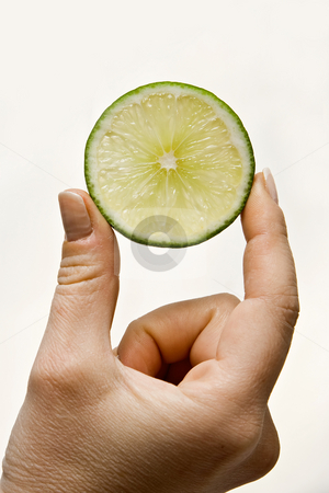 Lime slice in hand stock photo, Woman hand holding up a slice of lime, isolated on white by Paul Hakimata