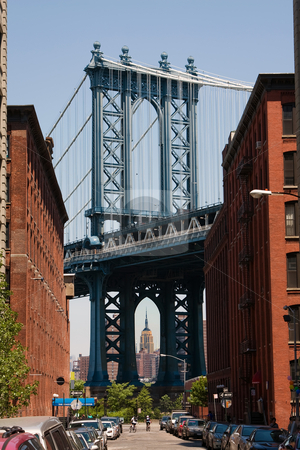 Manhattan Bridge stock photo, The Manhattan Bridge as seen from Brooklyn with the Empire State building underneath its arc. The street shows historic brownstone buildings used to be warehouses. by Paul Hakimata