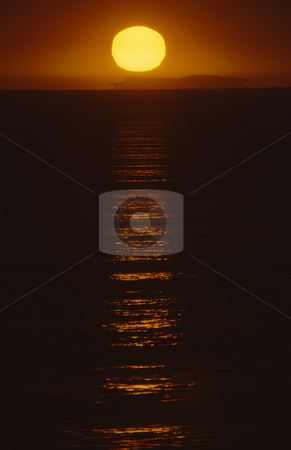 Sunset glow stock photo, Sunset at beach casting eerie glow over the water by Joseph Ligori
