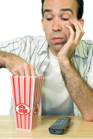 Boring Movie stock photo, A man eating popcorn while watching a boring movie by Richard Nelson