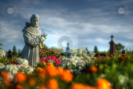 Statue Garden stock photo, A statue located in a cemetery surround by flowers by Richard Nelson