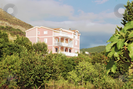 House on hill stock photo, Pink house on hill surrounded by green trees by Julija Sapic