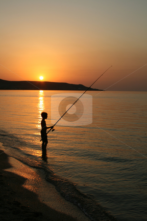 The silhouette of one fisherboy on the sea. stock photo, The silhouette of one fisherboy on the Sea of Azov against the background of the  sundown and mountains. by Viachaslau Barysevich