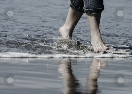 Beach Feet stock photo, Feet with cuffed jeans walking in water, with reflection on the beach. by Nikki Rose
