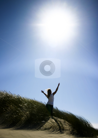 Woman Praise the Lord stock photo, Woman standing in tall grass on beach with arms raised to the sun. by Nikki Rose