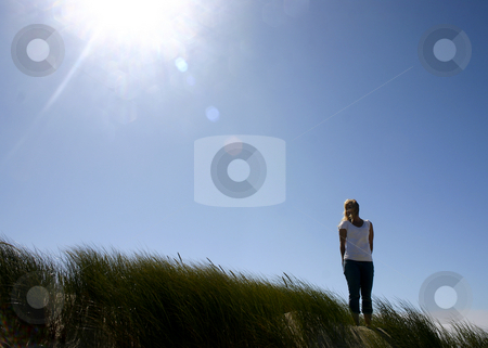 Woman In His Image stock photo, Woman standing in tall grass on the right with sunshining down from top left corner. by Nikki Rose