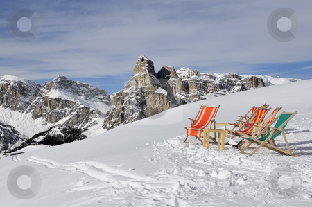 Deck chairs in the snow with the dolomites in the background, It stock photo, Deck chairs in the snow by Csaba Zsarnowszky