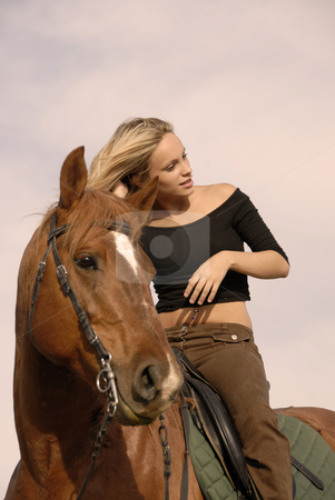 Blond riding girl stock photo, Riding girl and her brown stallion. focus on the teen by Bonzami Emmanuelle