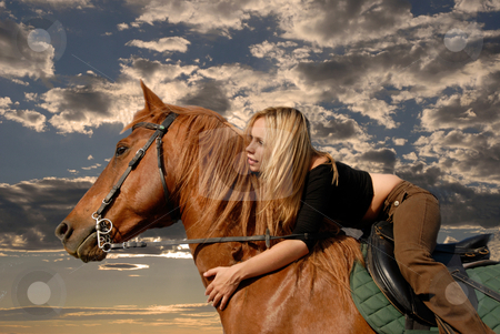 Riding girl stock photo, Young riding girl in a storm sky with her brown stallion by Bonzami Emmanuelle