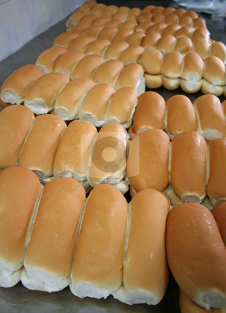 Bakery buns stock photo, Rows of bread loaves in racks in a bakery by Kheng Guan Toh