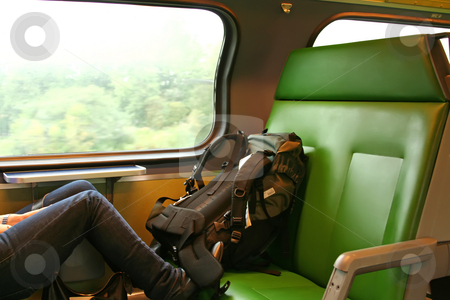Travelling backpacker stock photo, Female resting legs on a train seat with backpack by Kheng Guan Toh