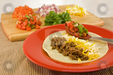 Mexican soft taco stock photo, Filling a flour tortilla with ground beef, cheese, and pico de Gallo by Lee Barnwell