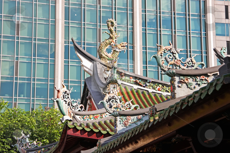 Chinese temple stock photo, Rooftop of traditional chinese temple against modern building by Kheng Guan Toh