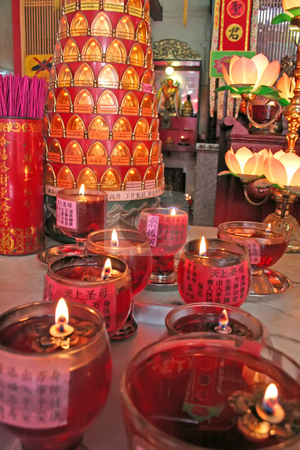 Chinese altar stock photo, Altar in a chinese temple with various offerings and candles by Kheng Guan Toh