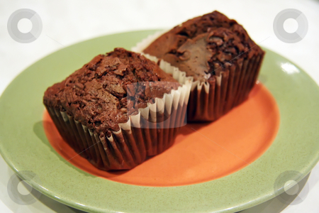 Chocolate muffins stock photo, Two chocolate muffins on an orange and green plate by Kheng Guan Toh