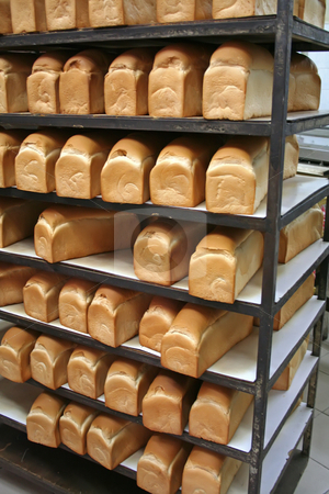 Bakery bread stock photo, Rows of bread loaves in racks in a bakery by Kheng Guan Toh