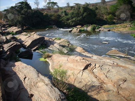 Huge boulders in the Athi River stock photo, A beautiful display of rocks and boulders in the Athi River in Kenya. by Rose Nthiwa