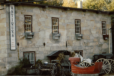 Antique Shop stock photo, Old antique shop with old carriages outside. Antique stone building. by Joseph Ligori