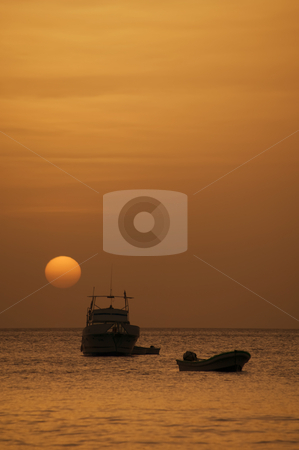 Boats at Sunset stock photo, Two boats in front of a setting sun at dusk by Scott Griessel
